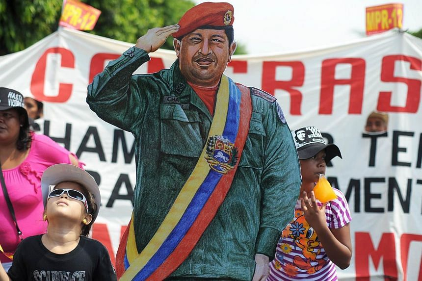 Girls participate in a traditional May Day rally with a life-size figure of the late president of Venezuela, Hugo Chavez, in San Salvador, on May 1, 2013. Venezuela's first standing statue of the late leftist leader Hugo Chavez will be erected in a s