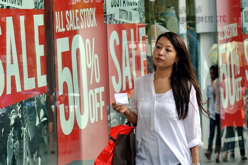A woman walking past advertisements for the Great Singapore Sale. Shoppers in Singapore spent more with their Mastercard credit cards during the first month of the Great Singapore Sale, the company said on Tuesday. -- BH FILE PHOTO: JOHARI RAHMAT