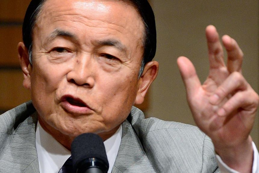 Japan's Finance and Deputy Prime Minister Taro Aso gestures as he delivers a speech in Tokyo on June 28, 2013. Mr Aso said on Tuesday the government may need to compile an extra budget to moderate fluctuations in the economy potentially caused by an