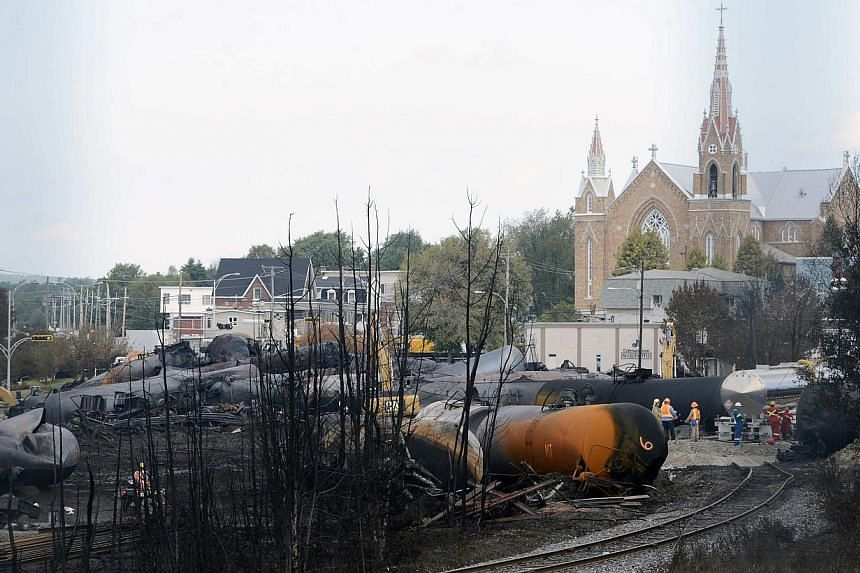 Wagons are pictured on the site of the train wreck in Lac-Megantic, on July 16, 2013. The Canadian government will offer C$60 million (S$73.2 million) to help rebuild the devastated Quebec town of Lac-Megantic, where 47 people died in a crude oil tan