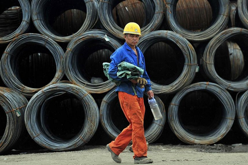 A labourer walks past piles of steel coils at a steel wholesale market in Shenyang, Liaoning province on July 15, 2013. China may use investments in high-speed railways to help digest an enduring capacity glut in steel, cement and other construction