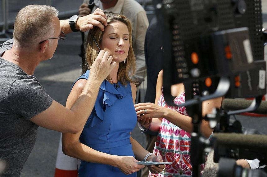 Makeup is applied to a television journalist in front of the Lindo Wing of St Mary's Hospital, where Britain's Catherine, Duchess of Cambridge arrived to give birth in London on July 22, 2013. -- PHOTO: REUTERS