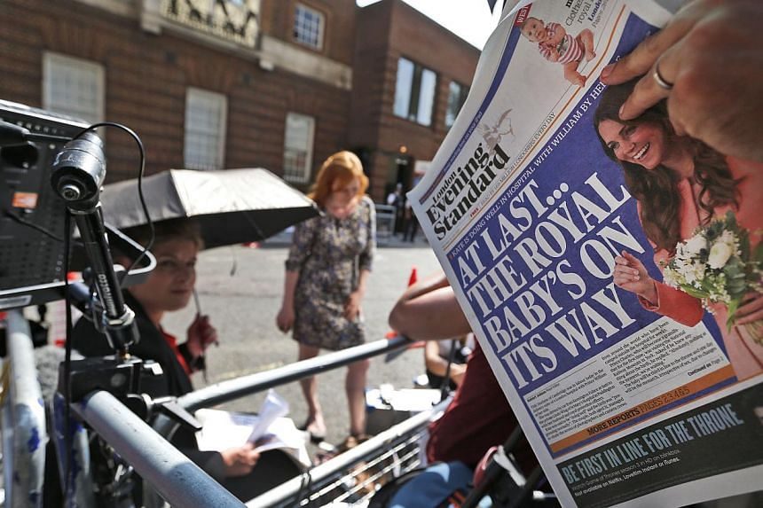 A news cameraman reads a newspaper across from St. Mary's Hospital's exclusive Lindo Wing in London, on Monday, July 22, 2013. -- PHOTO: AP