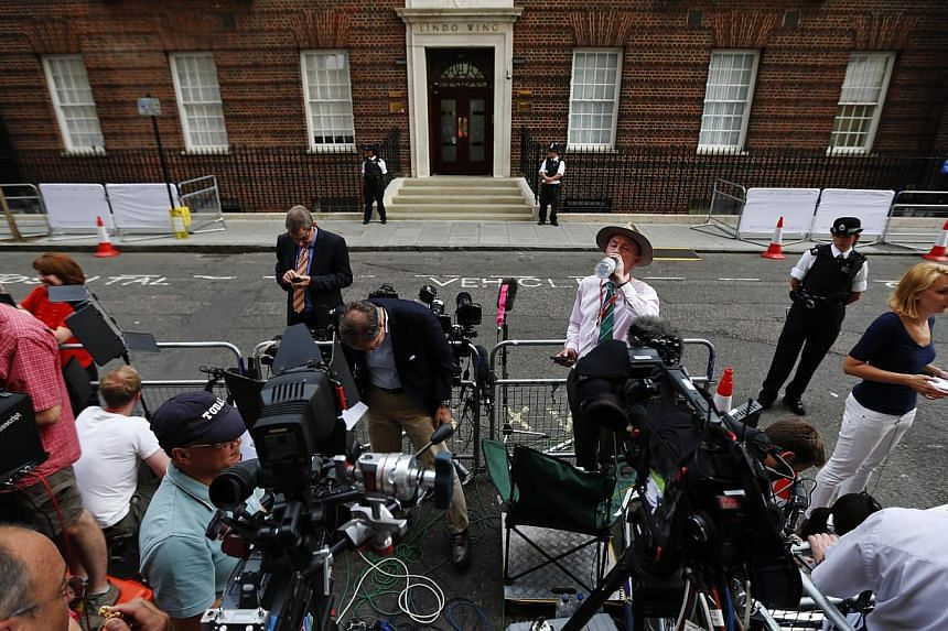 Members of the media wait across St. Mary's Hospital exclusive Lindo Wing in London, on Monday, July 22, 2013.  The world was awaiting the first glimpse of Britain's new prince on Tuesday with camera crews poised to photograph Prince Willia
