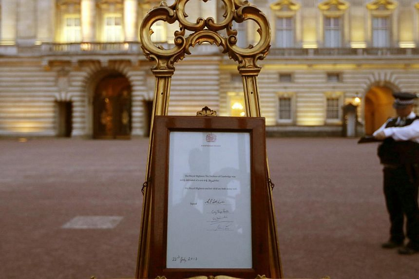 A notice proclaiming the birth of a baby boy of Prince William and Kate, Duchess of Cambridge, is display for the public view at Buckingham Palace in London on July 22, 2013. -- PHOTO: AFP
