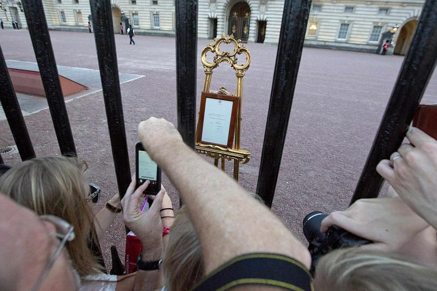 Crowds of people try to photogtraph a notice formally announcing the birth of a son to Britain's Prince William and Catherine, Duchess of Cambridge, placed in the forecourt of Buckingham Palace, in central London on July 22, 2013. -- PHOTO: REUTERS