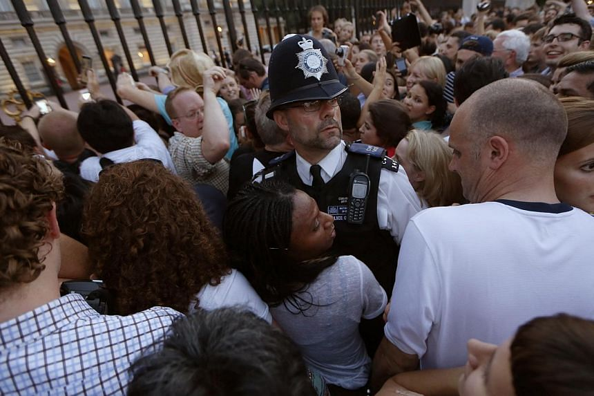 Spectators take photographs of the changing of the guard at Buckingham Palace on July 22, 2013, hours after the royal household announced that Kate, the Duchess of Cambridge had gone into labour. A joyful crowd popped corks, cheered and strained to g