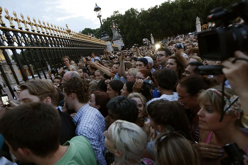 People gather to take a look of a notice proclaiming the birth of a baby boy to Prince William and Kate, Duchess of Cambridge, on display for public view at Buckingham Palace in London on July 22, 2013. -- PHOTO: AP