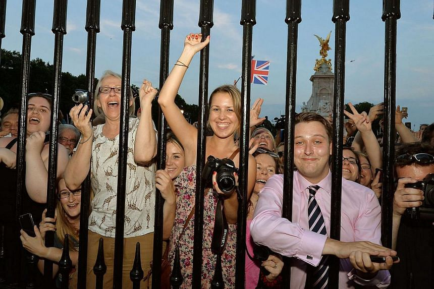 Crowds of people try to look at a notice formally announcing the birth of a son to Britain's Prince William and Catherine, Duchess of Cambridge, placed in the forecourt of Buckingham Palace, in central London on July 22, 2013. -- PHOTO: REUTERS