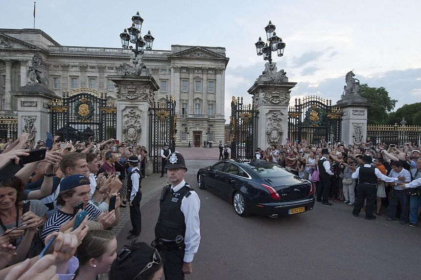 Crowds clamour to take pictures as a Jaguar car (centre) is driven on July 22, 2013, into the forecourt of Buckingham Palace in London, bringing the news of the birth of a baby boy, at 4.24pm to Prince William and Catherine, Duchess of Cambridge, at