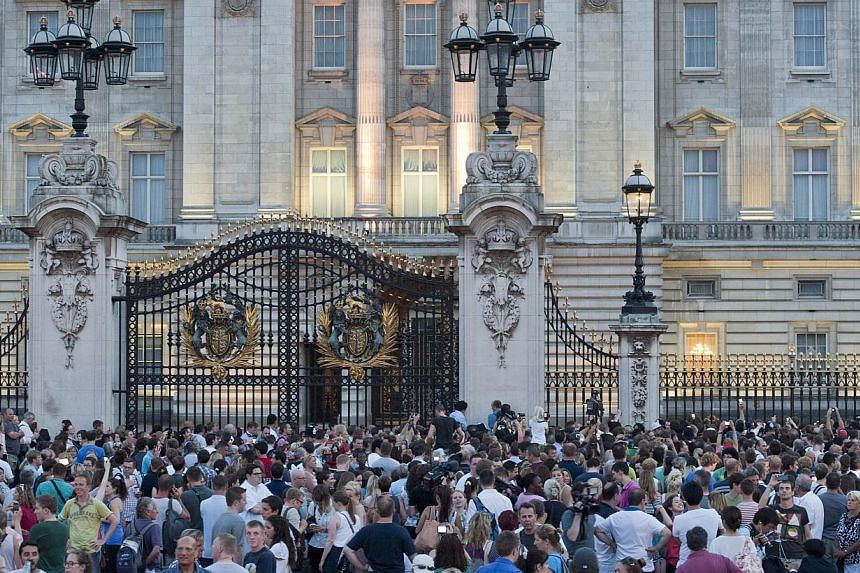 Crowds gather to see an easel in the forecourt of Buckingham Palace in London on July 22, 2013, announcing the birth of the son of Prince William and Catherine, Duchess of Cambridge. -- PHOTO: AFP