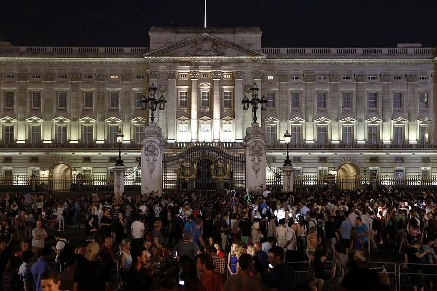People gather outside a floodlit Buckingham Palace in London to mark the birth of a baby boy to Prince William and Kate, Duchess of Cambridge, on July 22, 2013. Already touted as one of the most famous babies in the world, the first child of Bri