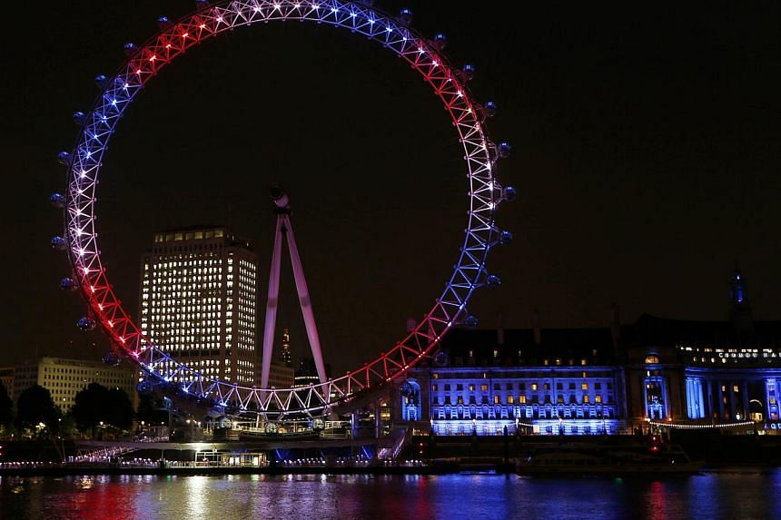 The London Eye observation wheel on the banks of the Thames is lit up in red, blue and white to mark the birth of a baby boy to Prince William and Kate, Duchess of Cambridge, in London on July 22, 2013. -- PHOTO: AP