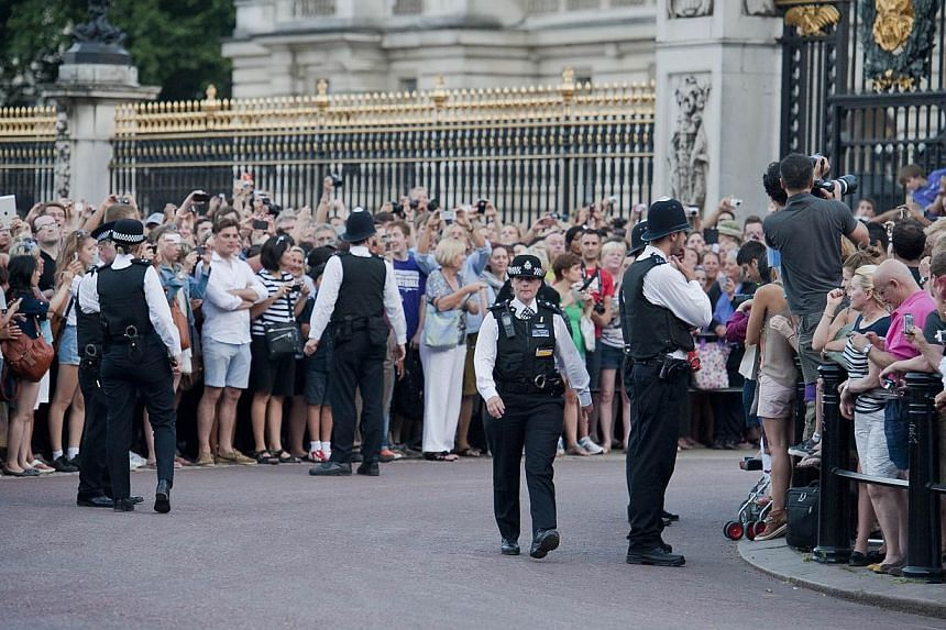 Crowds gather to see an easel in the forecourt of Buckingham Palace in London on July 22, 2013, announcing the birth of the son of Prince William and Catherine, Duchess of Cambridge. The joyous scenes of partying came after a sense of relief ear