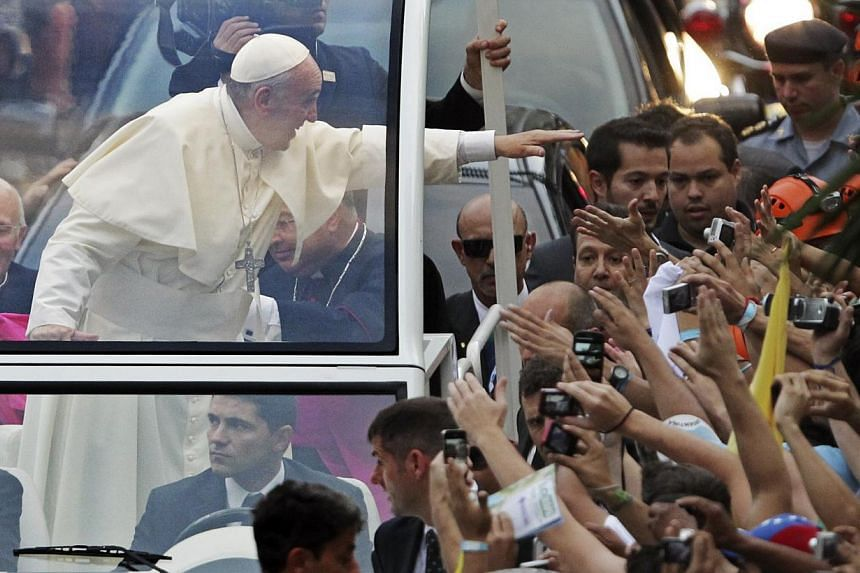 Pope Francis greets a crowd of the faithful from his Popemobile in downtown Rio de Janeiro on July 22, 2013. -- PHOTO: REUTERS
