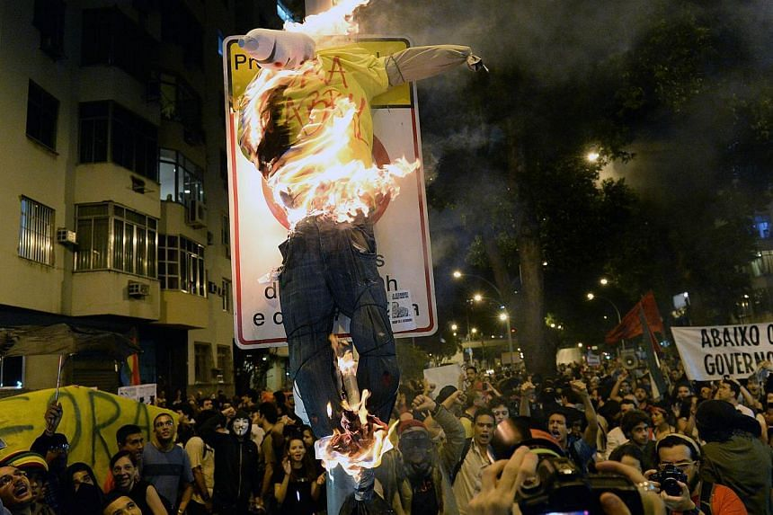 People burn an effigy of Rio de Janeiro's state Governor Sergio Cabral as atheists and the Anonymous protest group demonstrate against the money spent on the pope's visit, while Brazilian President Dilma Rousseff offers a welcoming ceremony for Pope