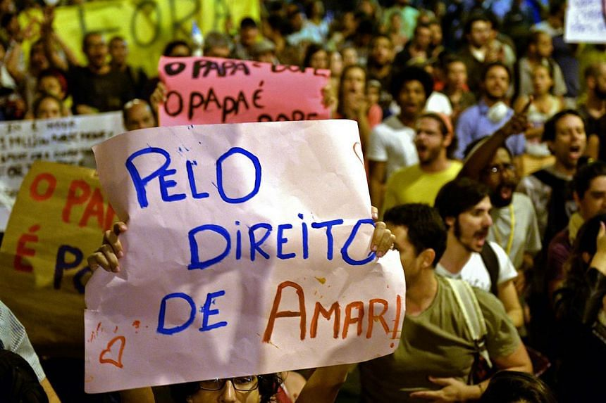 """A woman holds a poster reading """"For the right to love"""" as atheists, gay activists and members of the Anonymous protest group protest, while Brazilian President Dilma Rousseff offers a welcoming ceremony for Pope Francis at the Guanabara Palace, seat"""