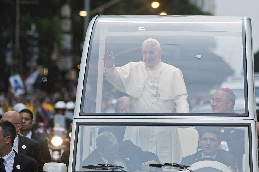 Pope Francis waves from his popemobile upon his arrival in Rio de Janeiro, Brazil, on Monday, July 22, 2013. -- PHOTO: AP