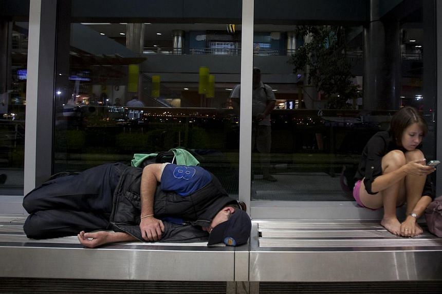 A passenger sleeps while another reads from her phone after being stranded at LaGuardia airport when their flights were cancelled when a Southwest Airlines 737 made an emergency landing in New York,on July 22, 2013.Several people were inj