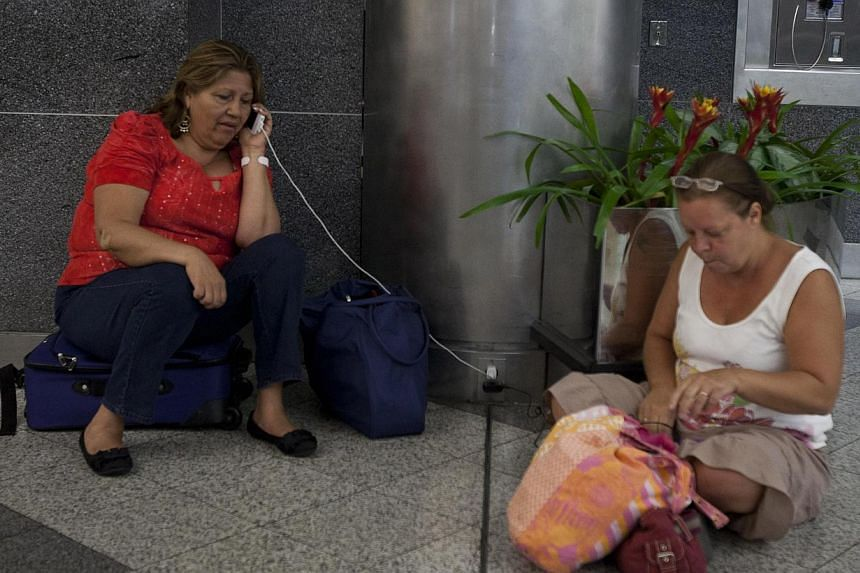 Stranded passengers, who had their flights cancelled when a Southwest Airlines 737 made an emergency landing, sit on the floor at LaGuardia airport in New York, on July 22, 2013. Several people were injured when a Southwest Airlines flight with 150 p