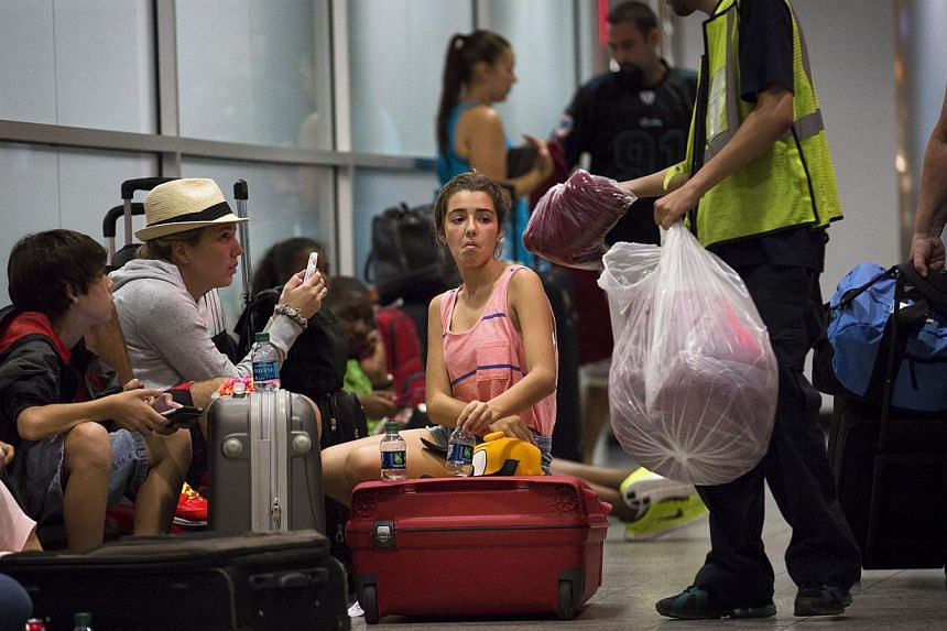 Stranded passengers are handed blankets while they wait at LaGuardia Airport as multiple flights were canceled after a Southwest Airlines 737 plane's nose gear collapsed during a landing, on Monday, July 22, 2013, in New York. Several people wer