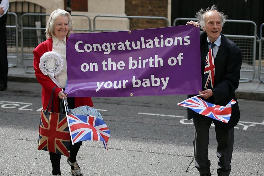 Royal enthusiasts unveil a banner congratulating Britain's Prince William and Kate, Duchess of Cambridge on the birth of the Prince of Cambridge, outside the entrance of the private Lindo Wing at St Mary's Hospital in London on Tuesday, July 23, 2013