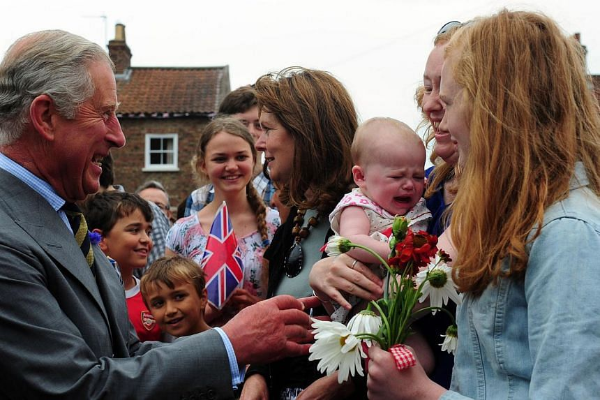 Britain's Prince Charles meets crowds of well wishers on a visit to Bugthorpe, England on Tuesday, July 23, 2013. Cheering crowds congratulated Prince Charles on Tuesday on the birth of his first grandson, although the heir to the throne and his wife