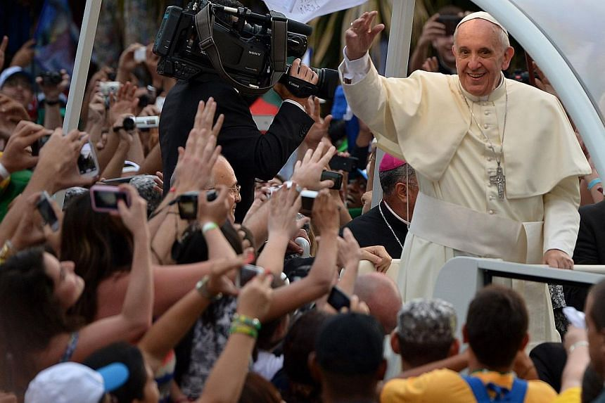 Pope Francis waves at faithfuls from the popemobile on his way to the Guanabara Palace after his arrival in Rio de Janeiro on Monday, July 22, 2013. Pope Francis's popularity on his Latin American home turf posed a challenge to Brazilian authorities