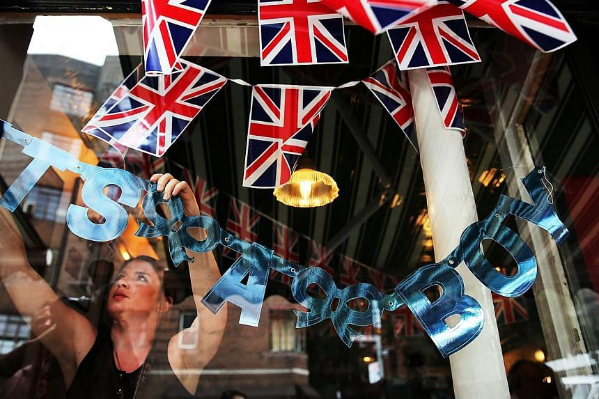 An employee at the British restaurant and grocery Tea & Sympathy, hangs a sign in the window celebrating the birth of Catherine, Duchess of Cambridge, and her husband Prince William's first child on July 22, 2013 in New York City. President Tony
