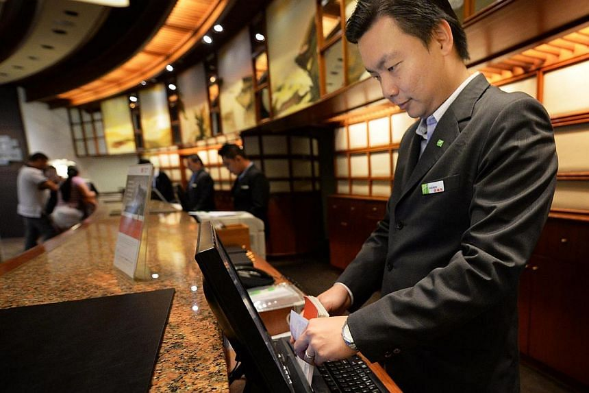 Mr Andrew Lee, 31, Rooms Division Manager at the Holiday Inn Singapore Atrium, using a passport/credit card scanner at the reception counter, which shortens each check-in by about two minutes. -- ST PHOTO: RAJ NADARAJAN
