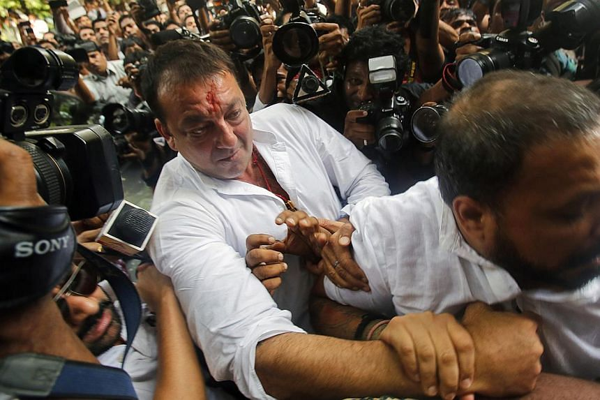 Bollywood actor Sanjay Dutt (centre) is escorted by his security staff as he arrives to surrender at a court in Mumbai on Thursday, May 16, 2013. Dutt, who is in jail for arms possession, lost his final appeal on Tuesday, July 23, 2013, against a dec