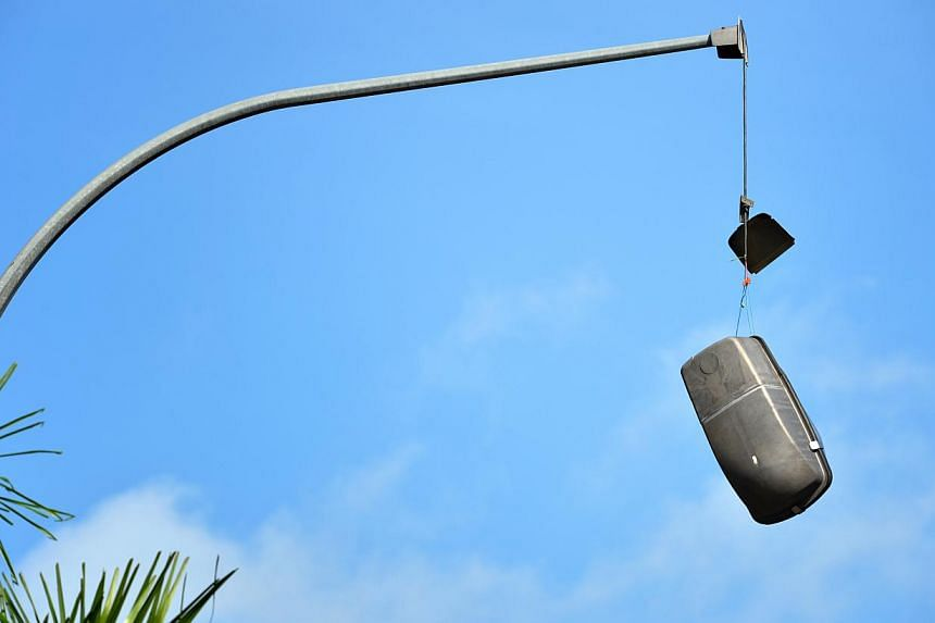 A man died after apparently losing control of his motorcycle and hitting his head against a lamp post on Tuesday morning along Braddell Road. The impact of the accident could have damaged the street lamp (above).-- ST PHOTO: KUA CHEE SIONG