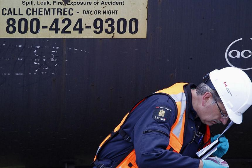 An inspector from Transport Canada takes notes from samples collected as part of their investigation in the train derailment in the town of Lac Megantic, Quebec on July 11, 2013. -- FILE PHOTO: REUTERS