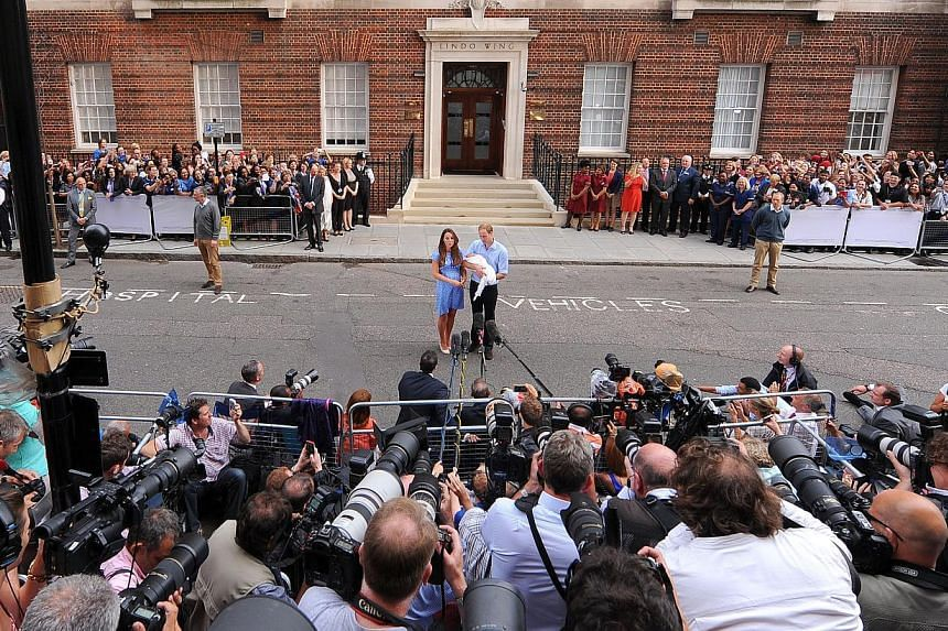 The Duke and Duchess of Cambridge pose for the media outside the Lindo Wing of St Mary's Hospital in London on July 23, 2013, carrying their newly born son, the Prince of Cambridge. The boy will be third in line to the British throne. -- PHOTO: AP