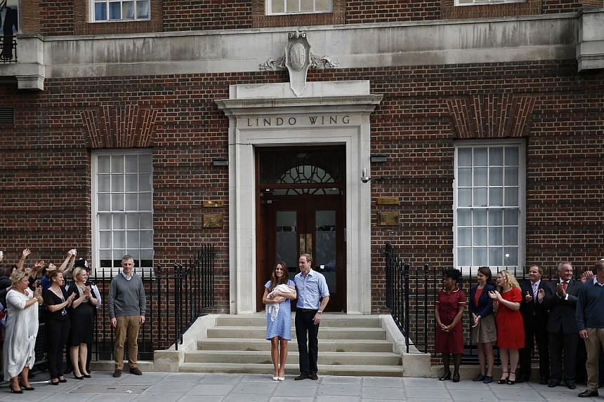 Britain's Prince William and Kate, Duchess of Cambridge, hold the Prince of Cambridge on July 23, 2013, outside St Mary's Hospital in London, where the Duchess gave birth on July 22. -- PHOTO: AP