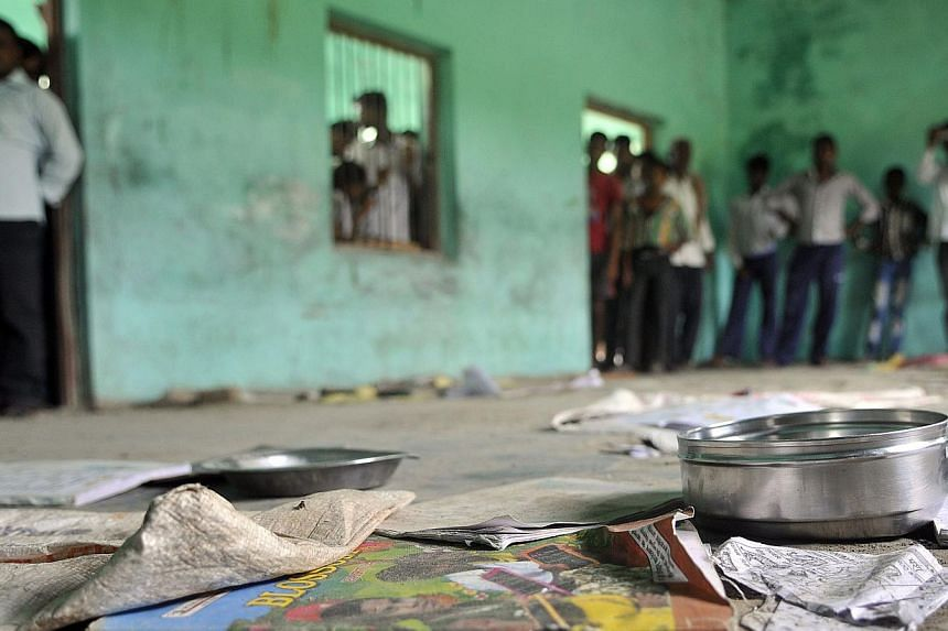 The scattered belongings of children who consumed a free mid-day meal, are seen in Dharma Sati village in the Saran district of Bihar state on Wednesday, July 17, 2013. Police on Wednesday, July 24, 2013, arrested the head of a school in eastern Indi