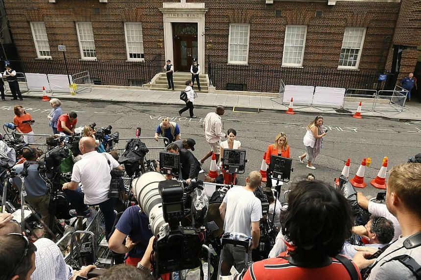 Members of the media wait in anticipation for Britain's Prince William and Kate, Duchess of Cambridge, to leave St. Mary's Hospital in London on Tuesday, July 23, 2013. -- FILE PHOTO: AP