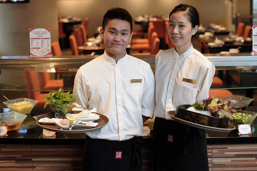Taiwanese service staff Chen Jhen Jie (left) and Chen Yea Ru work at Jumbo Group's steamboat restaurant Jpot. Restaurateurs say Taiwanese are keen to come here because of bleak job prospects at home.