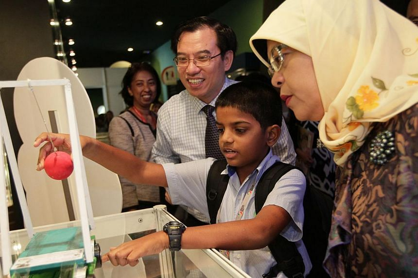 Speaker of Parliament Madam Halimah Yacob (right) watches as ten-year-old Ashutosh Menon Rajeev from The Global Indian International School demonstrates his toy, which won him the first prize in the Whizkid category of the Sony Creative Science Award