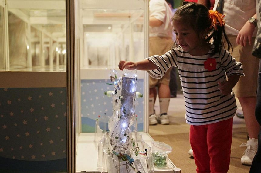 Twenty-two-month-old Courtney Jaz Suguitan, a sibling of one of the award winners, tries her hand at a toy made by Yoi Yam, a primary four student from Pei Chun Public School, during a tour of the winning toys at the Sony Creative Science Award 2013
