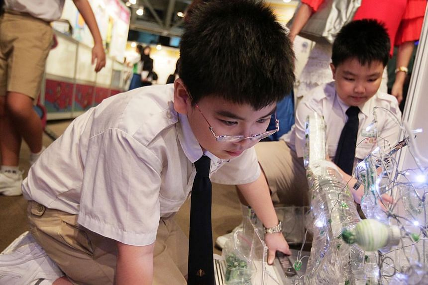 Yoi Yam (left), a primary four student from Pei Chun Public School, examines his toy called Dragonball Y, as his schoolmate and fellow participant Joel Koh, 8, looks on, during a tour of the winning toys at the Sony Creative Science Award 2013 on Wed