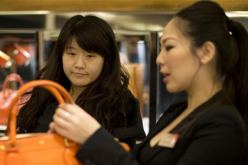 A Chinese customer shops at Harrods department store in London on Dec 10, 2012. Data shows spending by Chinese tourists rose 22 per cent, against 20 per cent in the first quarter. -- FILE PHOTO: AFP