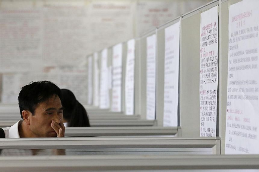 A job seeker looks at job advertisements at a job agency for service industry jobs in Beijing on July 17, 2013. China's employment situation in the second quarter was generally stable, the labour ministry said. -- FILE PHOTO: REUTERS