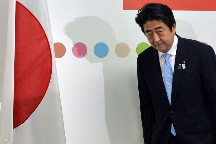 Japanese Prime Minister and ruling Liberal Democratic Party (LDP) leader Shinzo Abe bows his head to a Japanese national flag before starting a press conference at the LDP headquarters in Tokyo on July 22, 2013, one day after the Upper House election
