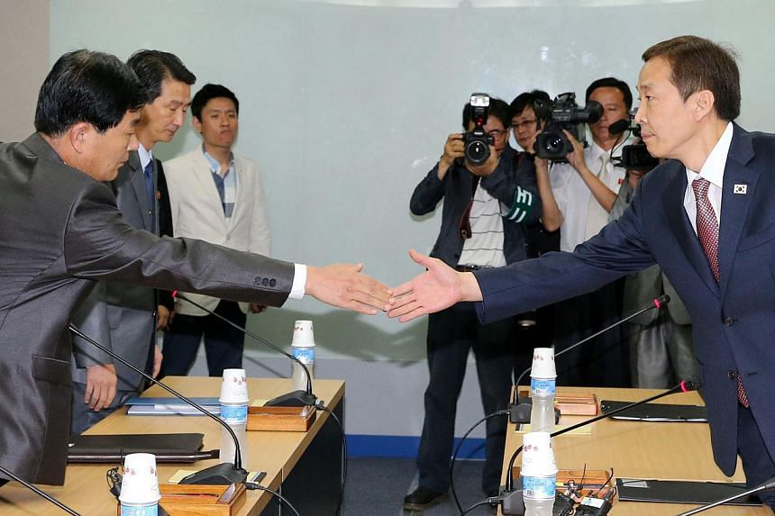 North Korea's chief delegate Pak Chol-Su (left) shakes hands with his South Korean counterpart Kim Ki-Woong (right) before a fifth round of talks at the Kaesong industrial complex in North Korea on July 22, 2013. -- FILE PHOTO: AFP