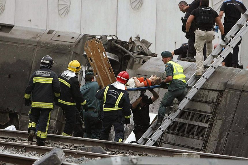 A woman is evacuated by emergency personnel at the scene of a train derailment in Santiago de Compostela, Spain, on July 24, 2013. At least 20 people died after a train derailed on Wednesday, local Galician television and the Cadena Ser radio st