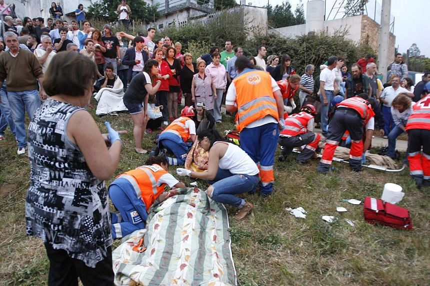 Emergency personnel respond to the scene of a train derailment in Santiago de Compostela, Spain, on July 24, 2013. At least 20 people died after a train derailed on Wednesday, local Galician television and the Cadena Ser radio station reported.