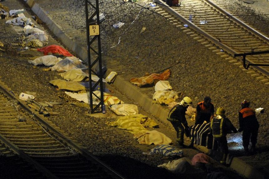 Rescuers carry the body of a victim as other bodies covered with blankets lie on the ground near the city of Santiago de Compostela on July 24, 2013. At least 20 people died after a train derailed on Wednesday, local Galician television and the Caden