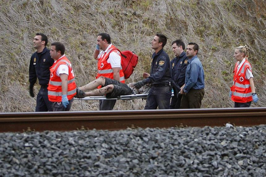 A man is evacuated by emergency personnel at the scene of a train derailment in Santiago de Compostela, Spain, on July 24, 2013. At least 20 people died after a train derailed on Wednesday, local Galician television and the Cadena Ser radio station r