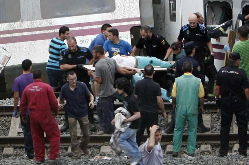 A wounded is evacuated by emergency personnel at the scene of a train derailment in Santiago de Compostela, Spain, on July 24, 2013. At least 20 people died after a train derailed on Wednesday, local Galician television and the Cadena Ser radio